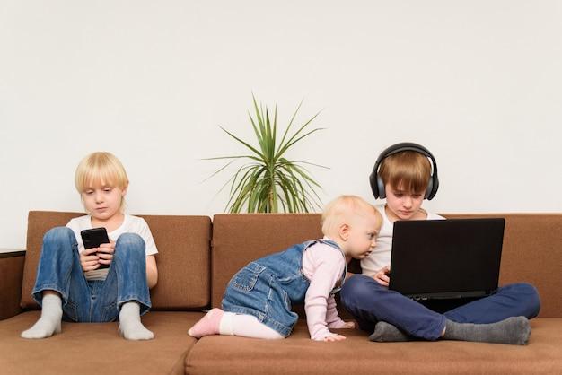 電話とラップトップが付いているソファーに3人の子供。アルファ世代と現代のテクノロジー。電子機器のある現代のライフスタイル。