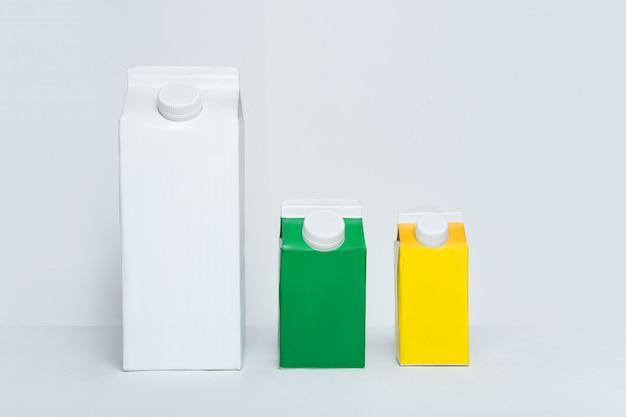 3つのカートンボックスまたは白いスペースにキャップが付いたテトラパックのパッケージ。