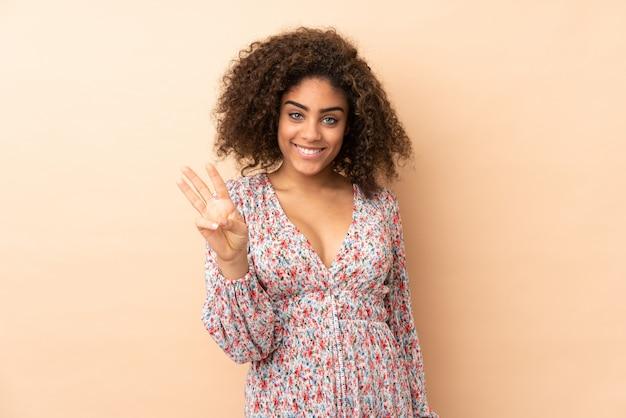 幸せと指で3つを数えるベージュの壁に若いアフリカ系アメリカ人女性
