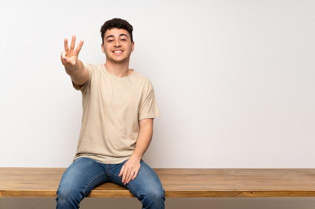 幸せなテーブルの上に座っていると指で3つを数える若い男