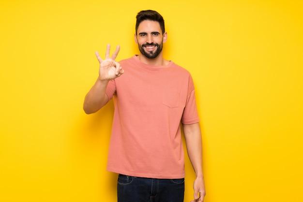 黄色の壁を越えて幸せと指で3つを数えてハンサムな男