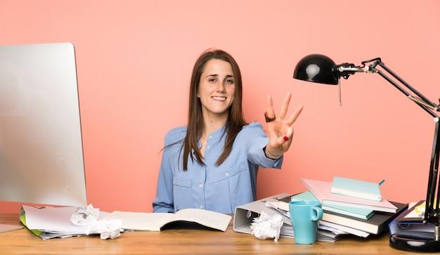 若い学生の女の子の幸せと指で3つを数える