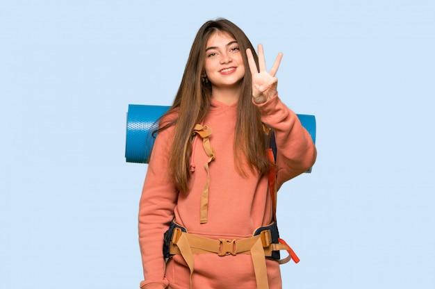 ハイカーの女の子幸せと青の指で3つを数える