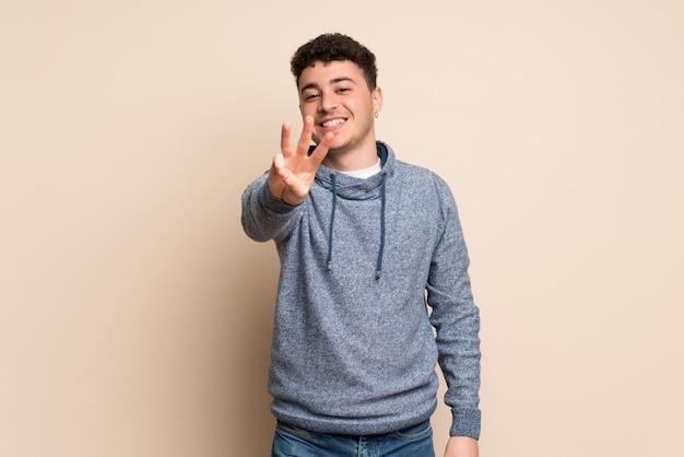 孤立した壁の幸せと指で3つを数える若い男