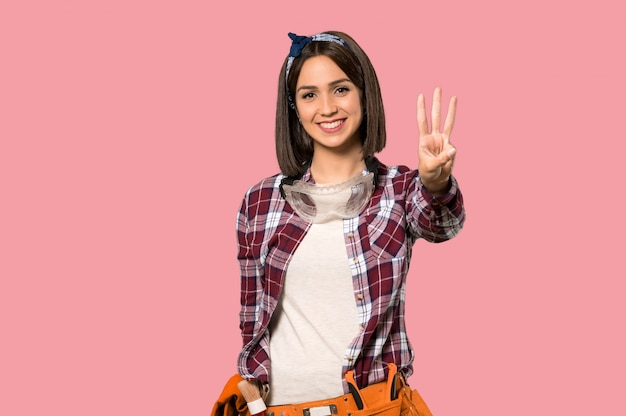 若くて幸せな女性と分離のピンクの壁に指で3つを数える女性