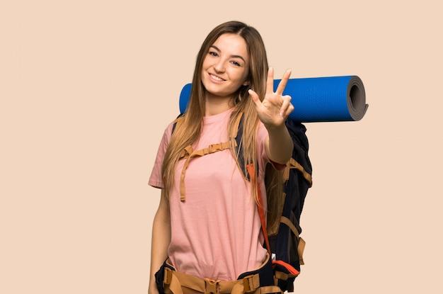 若いバックパッカーの女性の幸せと指で3つを数える
