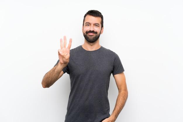 幸せと指で3つを数える孤立した白い壁の上の若いハンサムな男