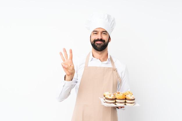 孤立した白い壁幸せと指で3つを数える上にマフィンケーキを保持している若い男