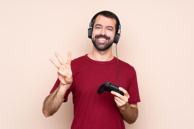 分離壁幸せと指で3つを数える上でビデオゲームコントローラーで遊ぶ男