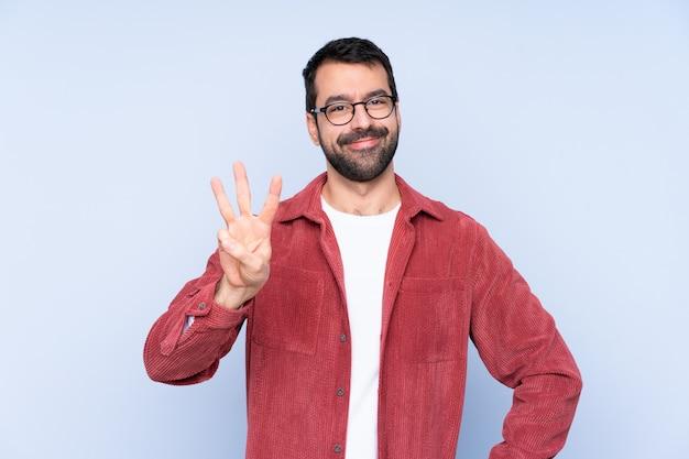 幸せと指で3つを数える青い壁にコーデュロイのジャケットを着ている若い白人男