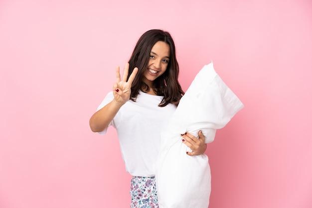 幸せと指で3つを数えるピンクの壁にパジャマの若い女性