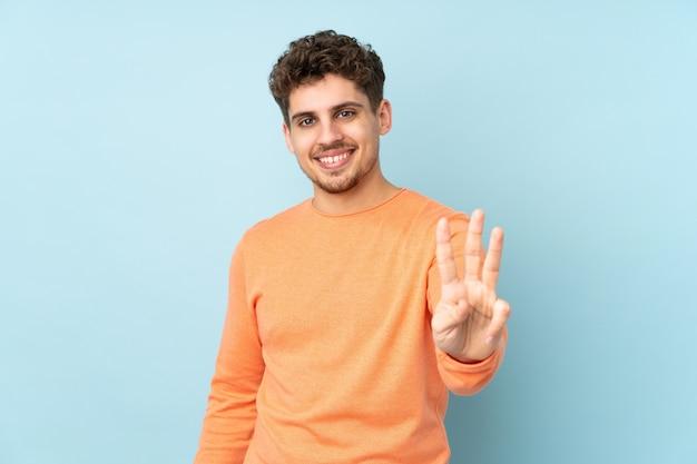 幸せと指で3つを数える青い壁に白人男性