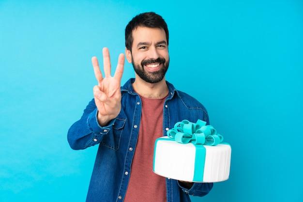 幸せと指で3つを数える分離の青い壁の上の大きなケーキを持つ若いハンサムな男