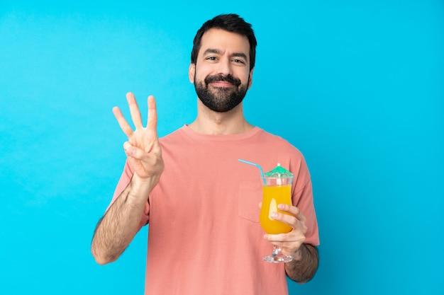 孤立した青い壁幸せと指で3つを数える上にカクテルをかざす以上の若い男