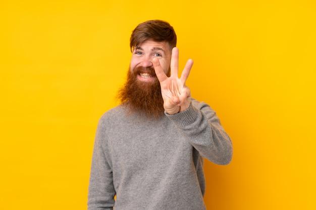 孤立した黄色の壁幸せと指で3つを数える上に長いひげを持つ赤毛の男