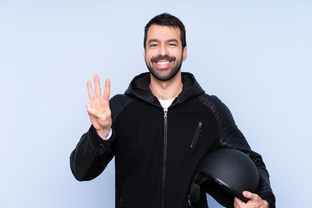 幸せと指で3つを数える隔離された壁の上のオートバイのヘルメットを持つ男