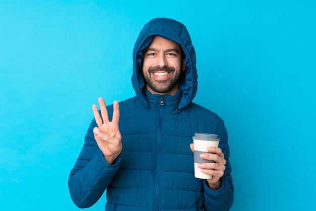冬のジャケットを着て幸せな分離の青い壁に持ち帰り用のコーヒーを保持し、指で3つを数える男