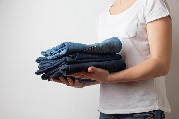 Руки крупного плана кавказские женские держа 3 пары голубых джинсов джинсовой ткани.