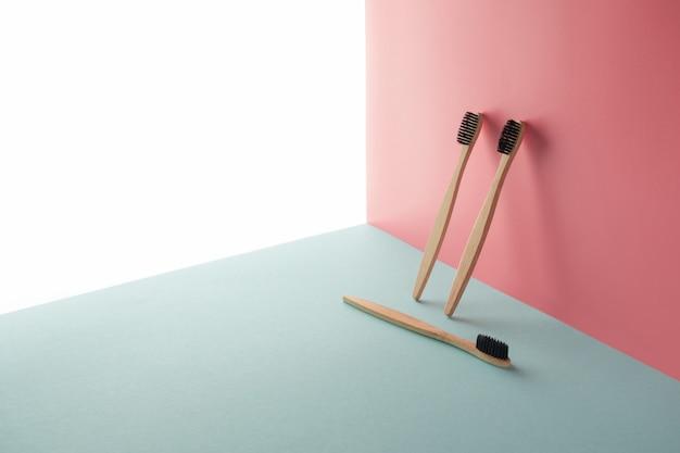 3つの竹、木製の歯ブラシは、白、青、ピンクの背景にあります。コピースペースの概念、幾何学的構成。医学概念、ブラッシング、環境に優しい、処理、堆肥