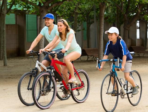 都市道路上の3つの自転車の陽気な家族