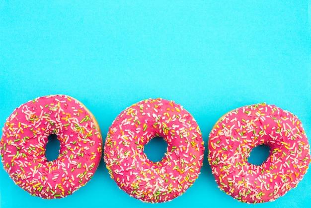 ターコイズブルーの背景に明るいピンクのアイシングで3つのドーナツ