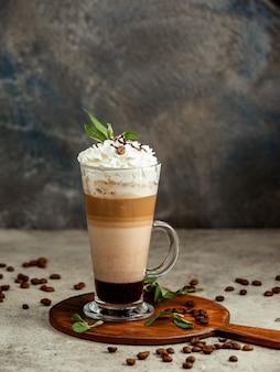 暗闇の中で3層コーヒーのカップ