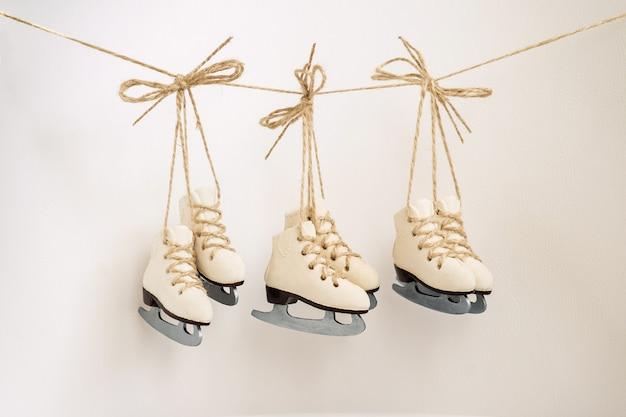 ロープの上のアイススケートの美しいクリスマスツリーの装飾小さな3ペア