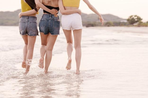 3つの幸せなアジアのガールフレンドグループの率直な背面図