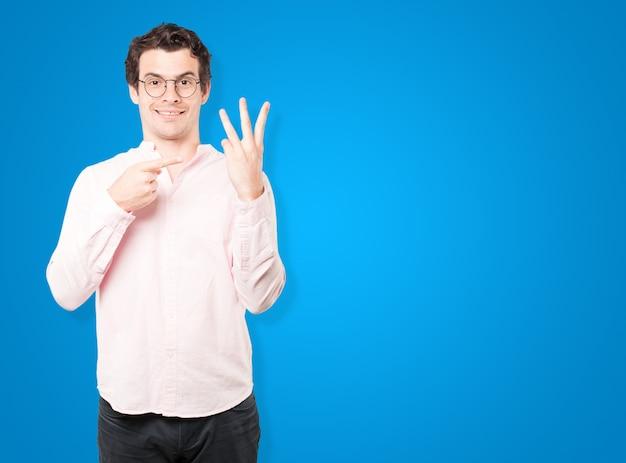番号3のジェスチャーを作る若い男