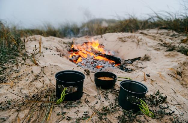 火が付いている砂の上に食べ物が3つの鍋