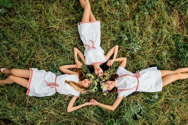 草の上に横たわる頭の上の花の花輪を持つ3つの民族の女の子のトップの肖像画。
