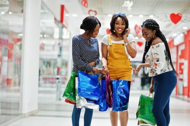 モールで色の買い物袋を持つ美しい3人の身なりの良いアフロアメリカンガールズの顧客。