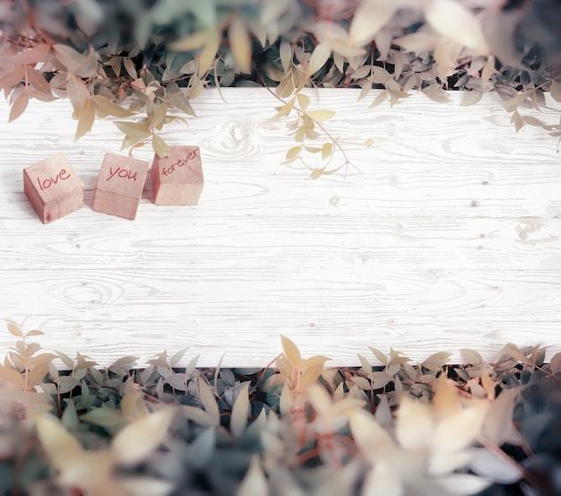 白い木、バレンタインデーの背景に「永遠に愛して」という言葉で3つの木製キューブ。