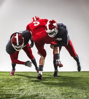 アクションの3人のアメリカンフットボール選手