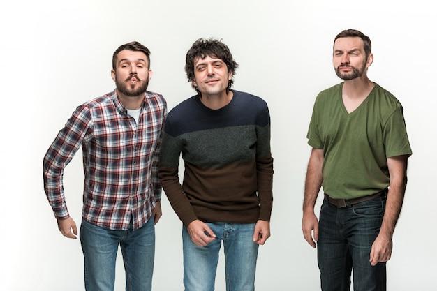 若い3人の男性が笑顔で、さまざまな感情で白の上に立っています。