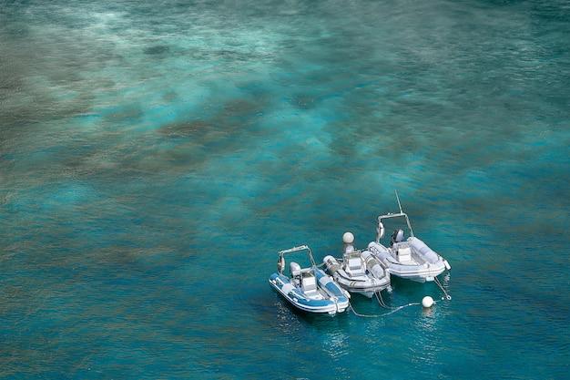 暖かい夏の日に、3つのインフレータブルモーターボートが海岸近くの湾に立ちます。