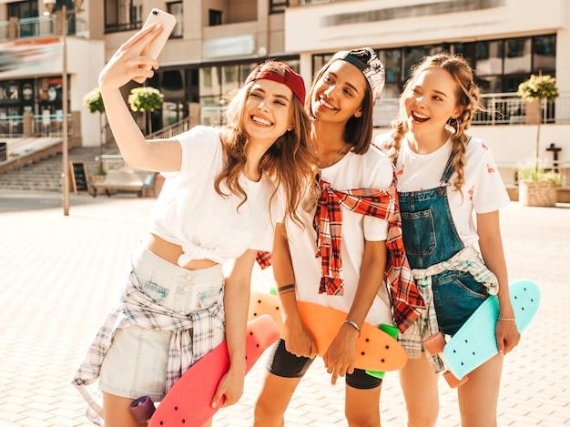カラフルなペニースケートボードと3人の若い笑顔の美しい女の子。通りの背景でポーズをとって夏の流行に敏感な服の女性。スマートフォンでセルフポートレート写真を撮る肯定的なモデル
