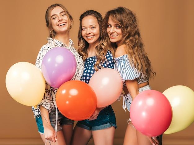格子縞のシャツの夏服で3人の笑顔の美しい女性。ポーズの女の子。カラフルな風船のモデル。楽しんで、お祝いの誕生日の準備ができて