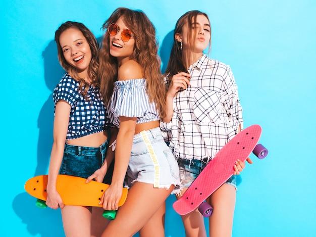 カラフルなペニースケートボードで3人の若いスタイリッシュなセクシーな笑顔の美しい女の子。夏の女性は、サングラスでポーズをとってシャツの服を格子縞。楽しいポジティブモデル