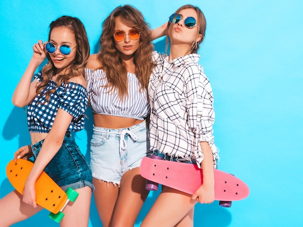 カラフルなペニースケートボードを持つ3人の若いスタイリッシュな笑顔の美しい女の子。サングラスでポーズをとって夏服の女性。楽しいポジティブモデル