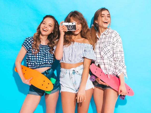 カラフルなペニースケートボードを持つ3つの美しいスタイリッシュな笑顔の女の子。夏の市松模様のシャツの女性。レトロな写真カメラで写真を撮る
