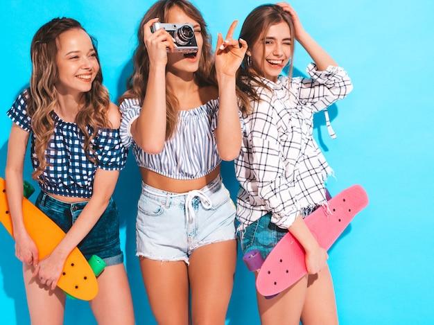 カラフルなペニースケートボードと3つのセクシーな美しいスタイリッシュな笑顔の女の子。夏の女性は格子縞のシャツ服ポーズします。レトロな写真カメラで写真を撮るモデル