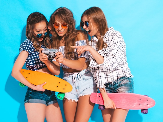 ペニースケートボードと3つの美しいスタイリッシュな笑顔の女の子。夏の市松模様のシャツの服とサングラスの女性。レトロな写真カメラで写真を撮る