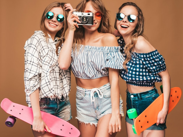 カラフルなペニースケートボードを持つ3つの美しいスタイリッシュな笑顔の女の子。夏の女性は格子縞のシャツ服ポーズします。レトロな写真カメラで写真を撮る