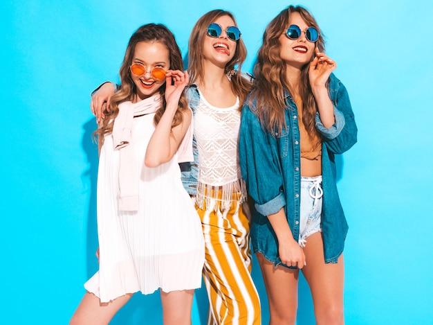 トレンディな夏のカジュアルな服装で3人の若い美しい笑顔の女の子。セクシーな屈託のない女性がポーズします。サングラスのポジティブモデル