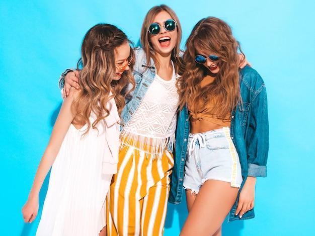 トレンディな夏カジュアルジーンズ服で3人の若い美しい笑顔の女の子。セクシーな屈託のない女性がポーズします。サングラスのポジティブモデル