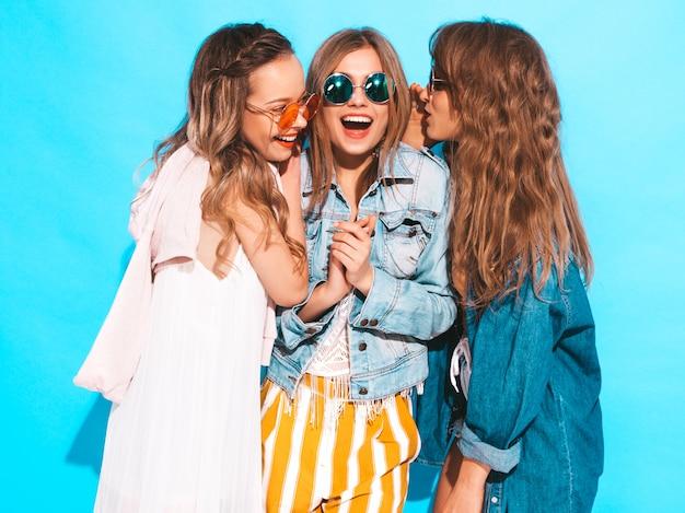 トレンディな夏のカジュアルな服装で3人の若い美しい笑顔の女の子。セクシーな女性は秘密を共有し、ゴシップ。青に分離。驚いた顔の感情