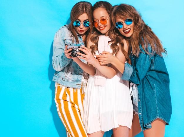 トレンディな夏のカラフルなドレスとサングラスの3人の若い美しい笑顔の女の子。セクシーな屈託のない女性がポーズします。レトロなカメラで写真を撮る