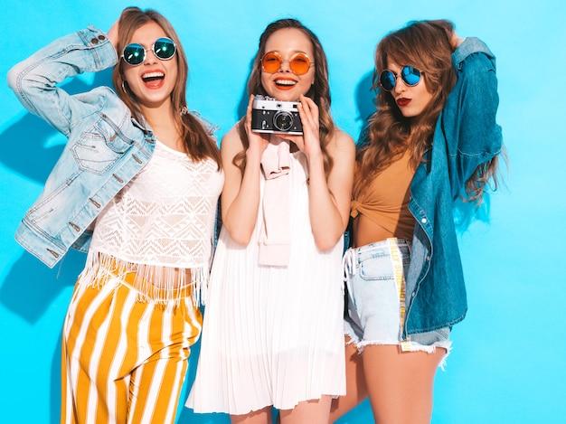 トレンディな夏のカジュアルドレスとサングラスの3人の若い美しい笑顔の女の子。セクシーな屈託のない女性がポーズします。レトロなカメラで写真を撮る