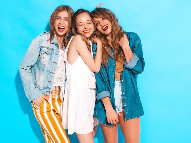 トレンディな夏カジュアルジーンズ服で3人の若い美しい笑顔の女の子。セクシーな屈託のない女性がポーズします。ポジティブモデル